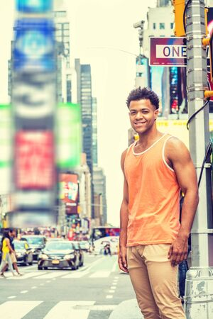 Young Happy Mix Race American Man traveling in New York City in hot summer, wearing orange tank top, beige pants, standing on intersection of street in Times Square of Manhattan, looking, smiling.