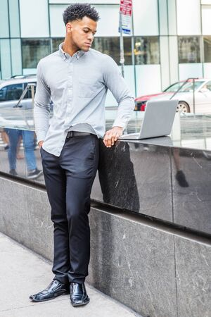Young Mix-Race American Man traveling, working in New York City, wearing light gray long sleeve shirt, black pants, leather shoes, standing on street by half marble wall, reading on laptop computer. Reklamní fotografie