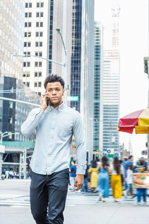 Young Mix Race American Man talking on cell phone, traveling in New York City, wearing long sleeve gray shirt, walking on street in Midtown of Manhattan. Modern high buildings and people on background