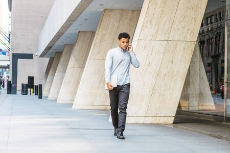 Young Mix Race American Man talking on phone, traveling, working in New York City, wearing gray shirt, black pants, leather shoes, carrying laptop computer, walking on street outside office building.