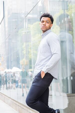 Young Mix Race American Man wearing light gray, long sleeve shirt, black pants, hand in pocket, standing against glass wall with reflections on street in Midtown of Manhattan, New York City, relaxing. Reklamní fotografie
