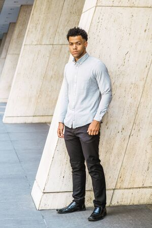 Portrait of Young Handsome American Man in New York City, wearing light gray long sleeve shirt, black pants, leather shoes, standing outside office building on street, confidently looking forward.