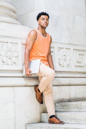 Young Mix-Race American college student studying in New York City, wearing orange tank top, beige pants, brown leather shoes, holding laptop computer, standing on stairs against wall on campus, think.