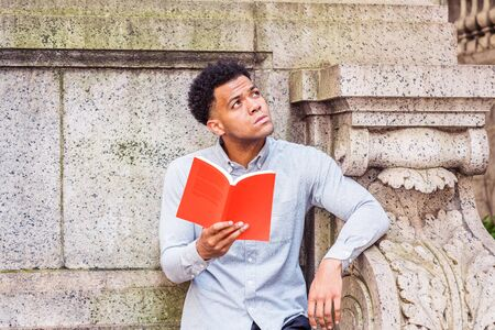 I Love Reading Book. Young American College Student studying in New York City, wearing light gray long sleeve shirt, standing in corner of wall on campus, hands holding red book, looking up, thinking. Stock Photo