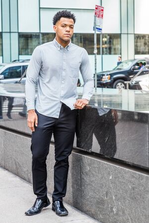 Young Handsome American Man traveling, relaxing in New York City, wearing light gray long sleeve shirt, black pants, leather shoes, standing by half marble wall on street, confidently looking forward. Stock Photo
