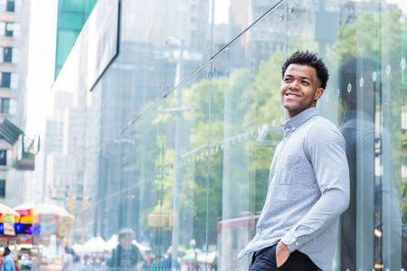 Young Mix Race American Man wearing light gray, long sleeve shirt, black pants, hand in pocket, standing against glass wall with reflections on street in Midtown of Manhattan, New York City, smiling. Reklamní fotografie