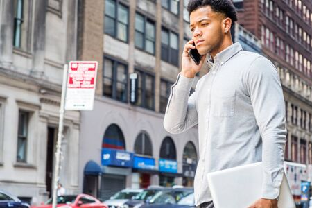 Young Mix Race American Businessman talking on cell phone, traveling in New York City, wearing gray shirt, carrying laptop computer, walking on street in Manhattan. Cars, buildings on background.