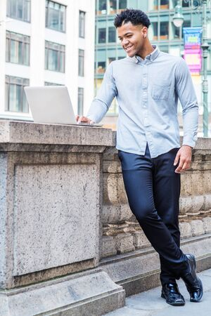 Young Mix-Race American College Student studying in New York City, wearing light gray long sleeve shirt, black pants, leather shoes, standing by half wall on campus, working on laptop computer, smile. Reklamní fotografie