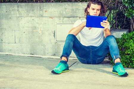 Modern Reading. Young Hispanic American Man with long brown curly hair, wearing white T shirt, blue jeans, green sneakers, sitting against wall in New York, looking down, reading blue tablet computer. Фото со стока