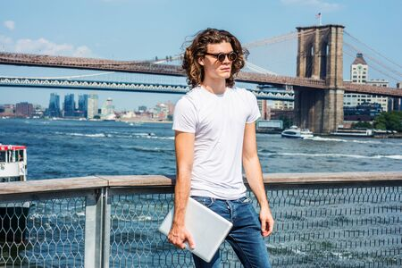 Young Hispanic American Man traveling in New York, with long hair, wearing sunglasses, white T shirt, holding laptop computer, standing by East River. Manhattan, Brooklyn bridges, boats on background.