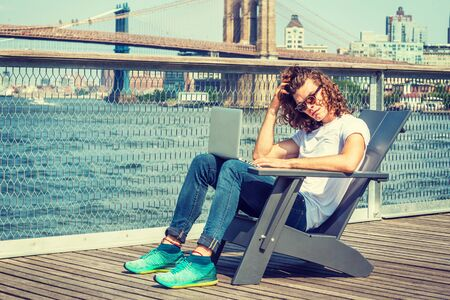 Young Hispanic American Man traveling in New York, with long hair, wearing sunglasses, white T shirt, jeans, sneakers, sitting on chair by river, working on laptop computer, scratching head, thinking. 写真素材 - 128970973