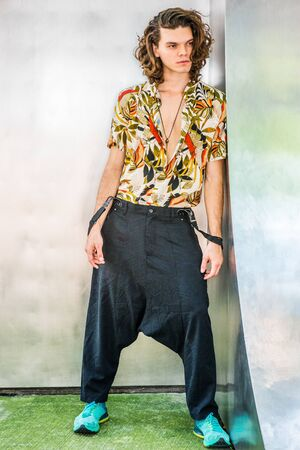 Hispanic American Artist with brown curly hair in New York, wearing colorful patterned short sleeve shirt, baggy loose pants with suspenders, patterned sneakers, hanging old key as necklace Фото со стока