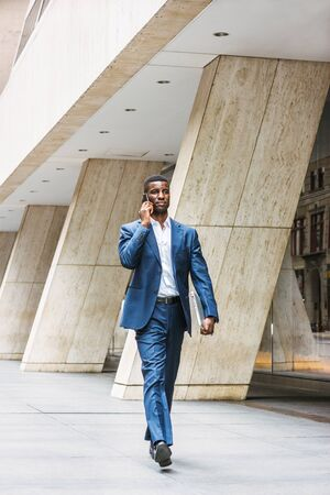 African American businessman traveling, working in New York, wearing blue suit, white undershirt, leather shoes, carrying laptop computer, walking on street outside office building, talking on phone. Stock Photo
