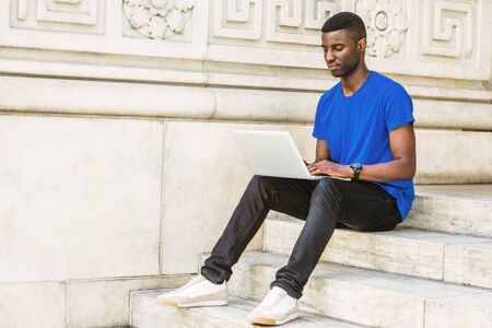 Young African American College Student studying in New York, wearing blue T shirt, black pants, sneakers, wristwatch, sitting on stairs outside office building, working on laptop computer on campus.