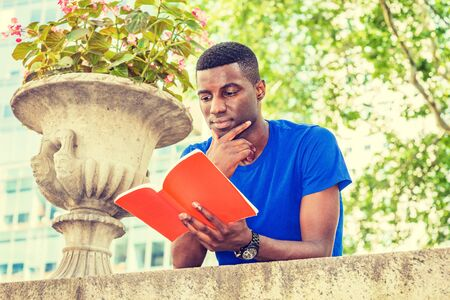 Young African American College Student studying in New York, wearing blue short sleeve T shirt, standing, back bending forward on top of wall on campus, holding red book, hand touching thin, reading.