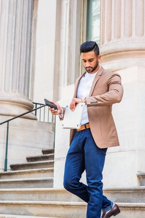 After work. Young East Indian American Businessman with beard, wearing brown blazer, blue pants, holding laptop computer, phone, raising arm, looking at wristwatch, walking down stairs from office.