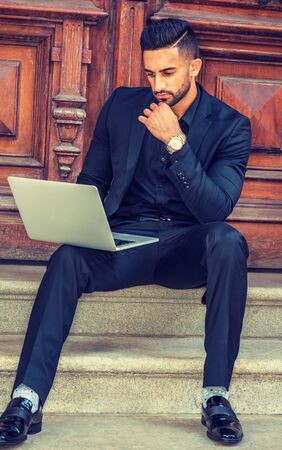 Way to Success. East Indian American Businessman with beard working in New York, wearing black suit, leather shoes, sitting on stairs of office doorway, working on laptop computer, hand touching chin.