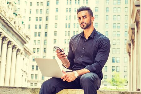 Way to Success. Young East Indian American Man with beard working on street in New York, wearing black shirt, holding laptop computer, sitting outside old style office building, texting on cell phone. Stock Photo