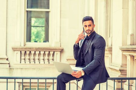 Young East Indian American Businessman with beard working in New York, wearing black suit, holding laptop computer, sitting on railing inside office building, looking away, talking on cell phone.
