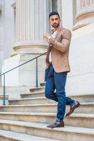 After work, Young East Indian American Businessman with beard, wearing brown blazer, white round collar shirt, blue pants, black leather shoes, walking down stairs from office building, looking away.