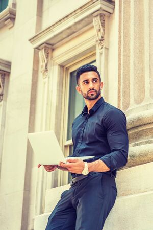 Way to Success. Young East Indian American Businessman with beard working in New York, wearing black shirt, holding laptop computer, standing outside old style office building, looking up, thinking. Stock Photo
