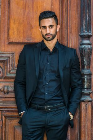Portrait of Young Handsome East Indian American Businessman with beard in New York, wearing black suit, black shirt, hands in pockets, standing by brown old style office doorway, looking at you.