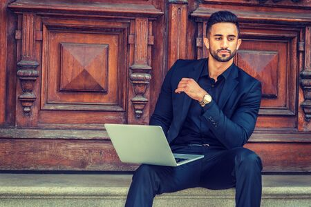 East Indian American Businessman with beard working in New York, wearing black suit, wristwatch, sitting on stairs of office doorway, working on laptop computer, narrowing eyes, looking down, thinking.