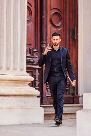Young East Indian American Businessman traveling, working in New York, with beard, wearing black suit, holding laptop computer, walking out from old style office building, talking on cell phone.