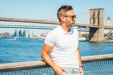 European Man traveling in New York, with beard, little gray hair, wearing white Polo shirt, sunglasses, standing by East River, looking around, thinking. Manhattan, Brooklyn bridges on background. 写真素材 - 128971640