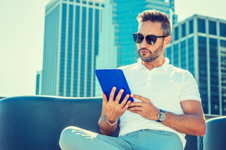 Modern Reading. Young European Man with beard, little gray hair, wearing white Polo shirt, sunglasses, sitting in business district with high buildings in New York City, reading blue tablet computer. Фото со стока