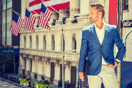 Young European Businessman with beard traveling, working in New York, wearing blue blazer, white shirt, holding briefcase, standing outside office building with American flags, looking forward.