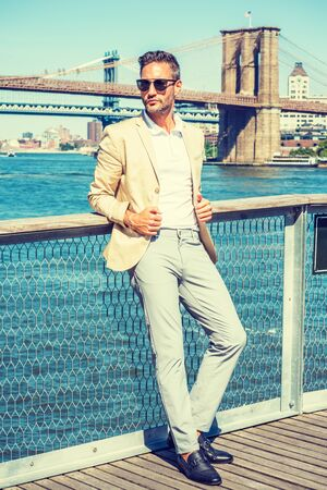 European Man traveling in New York, with beard, little gray hair, wearing beige blazer, gray pants, black leather shoes, sunglasses, standing by East River. Manhattan, Brooklyn bridges on background. 写真素材