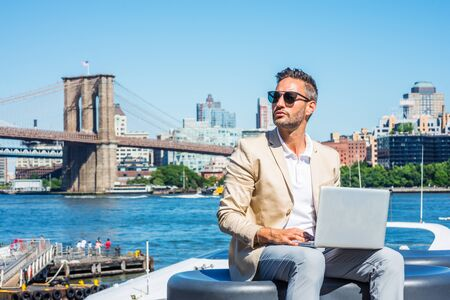 Young European Businessman traveling, working in New York, with beard, little gray hair, wearing beige blazer, sunglasses, sitting by river, working on laptop computer. Brooklyn bridge on background. 写真素材
