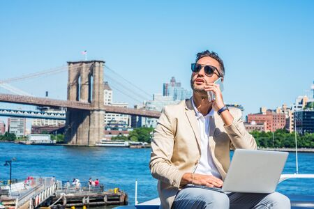 Young European Businessman traveling, working in New York, with beard, little gray hair, wearing beige blazer, sunglasses, sitting by East River, working on laptop computer, talking on cell phone.
