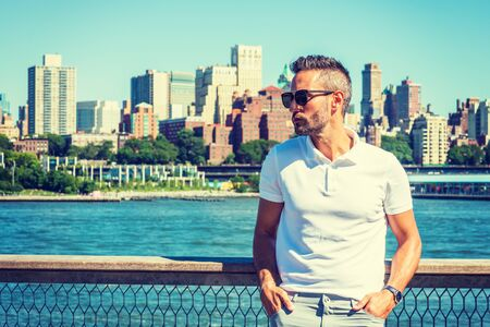 Young European Man traveling in New York, with beard, little gray hair, wearing white Polo shirt, sunglasses, standing by East River, looking around, thinking. Brooklyn buildings on far background. 写真素材 - 128971770