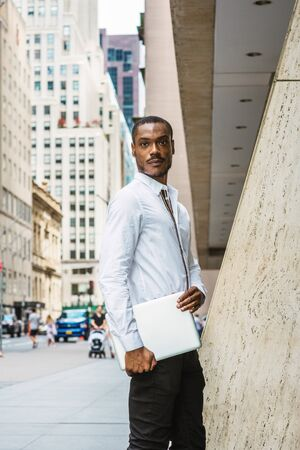 Young African American businessman with beard traveling, working in New York, wearing white shirt, carrying laptop computer, standing on street in Manhattan, looking. Cars, buildings on background.
