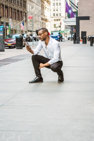 Young African American Man with beard, wearing white shirt, black pants, leather shoes, squatting on street in Manhattan, New York, reading messages on cell phone. Cars, buildings on background