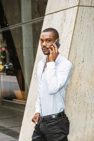 Phone call outside. Young African American businessman with beard, wearing white shirt, standing on street outside office building in New York City,  talking on cell phone,