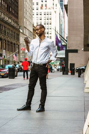 Young African American Man with beard, wearing white shirt, black pants, leather shoes, standing on street in Manhattan, New York, reading messages on cell phone. People, cars, buildings on background