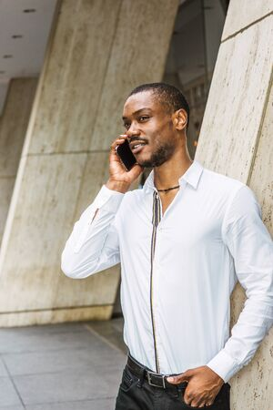Phone call outside. Young African American businessman with beard, wearing white shirt, standing on street outside office building in New York City, looking, smiling, talking on cell phone.
