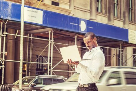 Young African American businessman traveling, working in New York City, wearing white shirt, hands holding laptop computer, walking on street, looking down, reading. Cars, buildings on background.
