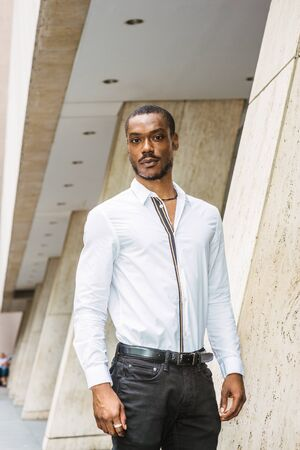 Portrait of Young African American Man in New York City. Young black guy with beard, wearing white long sleeve shirt, black pants, standing outside office building, confidently looking forward. Stockfoto