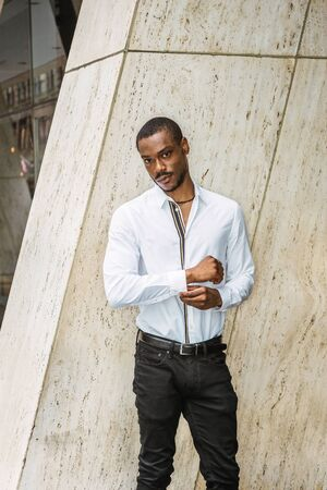 Portrait of Young African American Man in New York City. Young black guy with beard, wearing white long sleeve shirt, black pants, standing outside office building, hand touching cuff, looking at you.