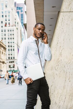 Young African American businessman with beard talking on cell phone, traveling in New York, wearing white shirt, carrying laptop computer, walking on street in Manhattan, listening, seriously thinking