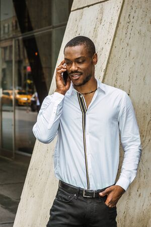 Phone call outside. Young African American businessman with beard, wearing white shirt, standing on street outside office building in New York City, looking down, smiling, talking on cell phone.