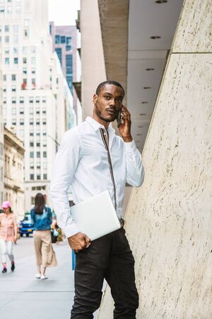 Young African American businessman with beard talking on cell phone, traveling in New York, wearing white shirt, carrying laptop computer, walking on street in Manhattan. Cars, buildings on background. Stockfoto