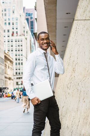 Young Happy African American businessman with beard talking on cell phone, traveling in New York, wearing white shirt, carrying laptop computer, walking on street with high buildings in Manhattan.