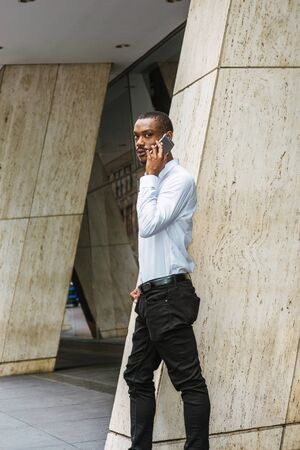 Phone call outside. Young African American businessman with beard talking on cell phone, traveling in New York City, wearing white shirt, black pants, walking out from office building