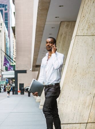 Young African American businessman traveling, working in New York, wearing white shirt, black pants, carrying laptop computer, walking out from office building to street, talking on cell phone. Stockfoto