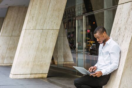 Young African American businessman working in New York, wearing white shirt, black pants, standing against column outside office building, looking down, frowned, working on laptop computer, thinking.